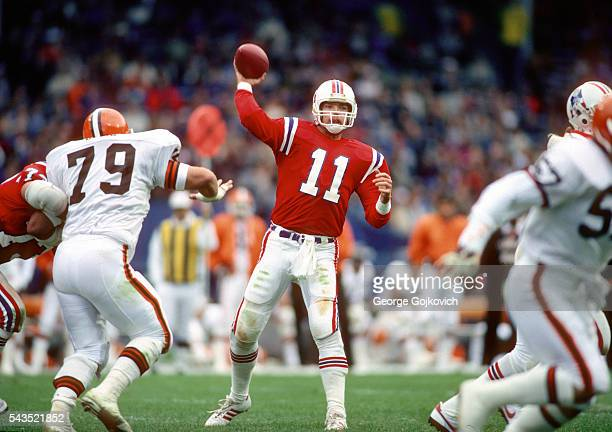 Quarterback Tony Eason of the New England Patriots passes while under pressure from defensive lineman Bob Golic of the Cleveland Browns during a...