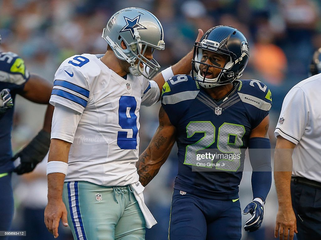 Quarterback Tony Romo #9 of the Dallas Cowboys is met by free safety Earl Thomas #29 of the Seattle Seahawks as he leaves the field after being injured in the first quarter at CenturyLink Field on August 25, 2016 in Seattle, Washington.