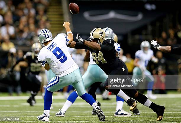 Quarterback Tony Romo of the Dallas Cowboys is pressured by defensive end Cameron Jordan of the New Orleans Saints during a game at the MercedesBenz...