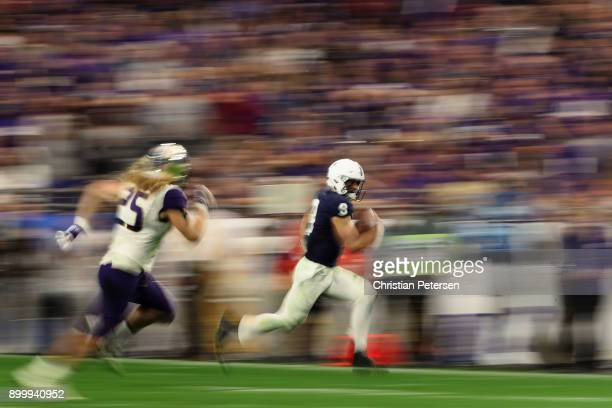 Quarterback Trace McSorley of the Penn State Nittany Lions scrambles with the football ahead of linebacker Ben BurrKirven of the Washington Huskies...