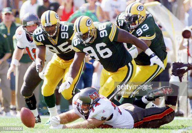 Quarterback Trent Dilfer of the Tampa Bay Buccaneers watches as teammate Paul Gruber dives for a Dilfer's fumble as Keith McKenzie Vaugh Booker and...
