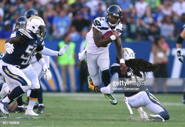 Quarterback Trevone Boykin of the Seattle Seahawks runs for the first down as he tackled defensive back Tre Boston of the Los Angeles Chargers during...