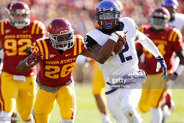 Quarterback Trevone Boykin of the TCU Horned Frogs rushes the ball into the end zone for a touchdown as defensive back Deon Broomfield of the Iowa...