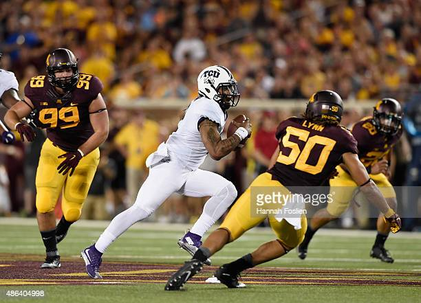 Quarterback Trevone Boykin of the TCU Horned Frogs scrambles with the ball against Andrew Stelter Jack Lynn and Julian Huff of the Minnesota Golden...