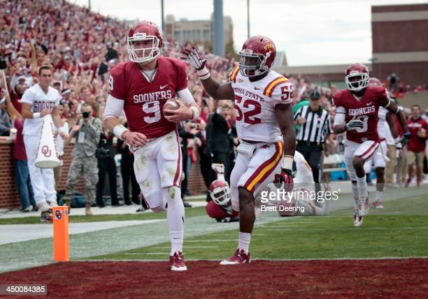 Quarterback Trevor Knight of the Oklahoma Sooners scores a touchdown in front of linebacker Jeremiah George of the Iowa State Cyclones November 16...