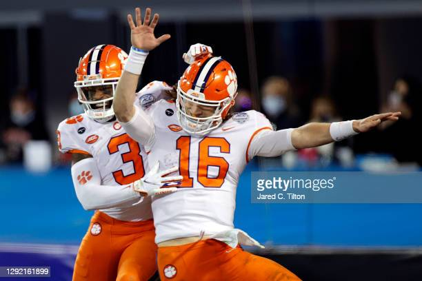 Quarterback Trevor Lawrence of the Clemson Tigers celebrates with wide receiver Amari Rodgers after scoring a 34-yard rushing touchdown in the third...