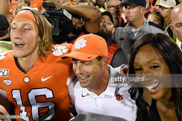 Quarterback Trevor Lawrence of the Clemson Tigers head coach Dabo Swinney of the Clemson Tigers and ESPN analyst Maria Taylor embrace at midfield as...