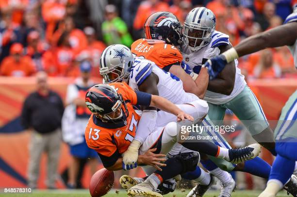 Quarterback Trevor Siemian of the Denver Broncos is sacked by defensive end Demarcus Lawrence of the Dallas Cowboys forcing a fumble and turnover in...