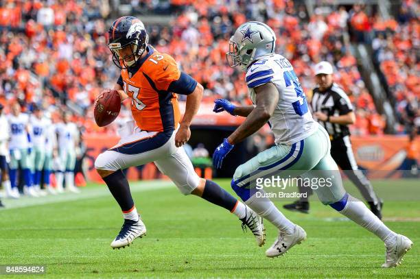 Quarterback Trevor Siemian of the Denver Broncos keeps the ball and is chased by strong safety Kavon Frazier of the Dallas Cowboys in the second...