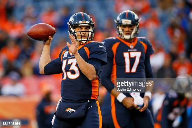 Quarterback Trevor Siemian of the Denver Broncos warms up as backup Quarterback Brock Osweiler of the Denver Broncos looks on before a game against...