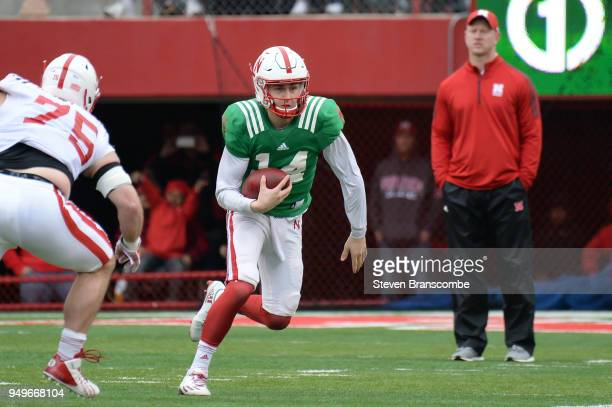 Quarterback Tristian Gebbia of the Nebraska Cornhuskers runs as Head Coach Scott Frost watches during the Spring game at Memorial Stadium on April 21...
