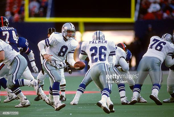 Quarterback Troy Aikam of the Dallas Cowboys turns to hand the ball off to Paul Palmer against the New York Giants during an NFL football game...