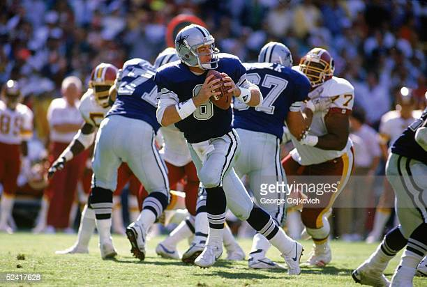Quarterback Troy Aikman of the Dallas Cowboys drops back to pass during an NFL game against the Washington Redskins on September 23 1990 at RFK...