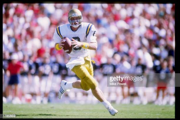 Quarterback Troy Aikman of the UCLA Bruins runs down the field during a game against the Arizona Wildcats at Arizona Stadium in Tucson Arizona UCLA...