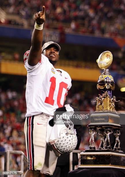Quarterback Troy Smith of the Ohio State Buckeyes points towards the crowd as he stands next to the trophy after the Buckeyes defeated the Notre Dame...