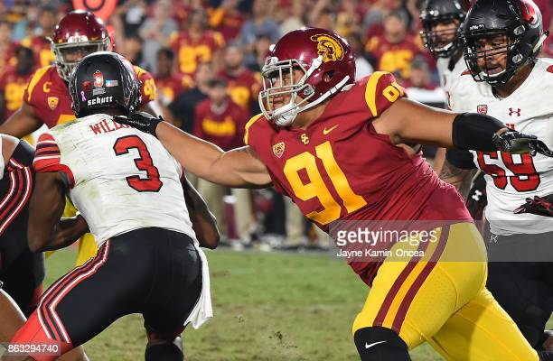 Quarterback Troy Williams of the Utah Utes avoids a tackle by defensive tackle Brandon Pili of the USC Trojans in the game at the Los Angeles...