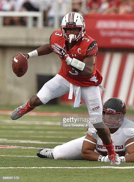 Quarterback Troy Williams of the Utah Utes avoids the tackle by Anu Poleo of the Southern Utah Thunderbirds in the first quarter at RiceEccles...