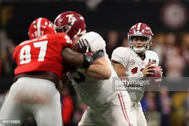 Quarterback Tua Tagovailoa of the Alabama Crimson Tide drops back to pass as nose tackle John Atkins of the Georgia Bulldogs during the CFP National...