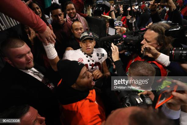 Quarterback Tua Tagovailoa of the Alabama Crimson Tide is surrounded by fans and media after defeating the Georgia Bulldogs in the CFP National...
