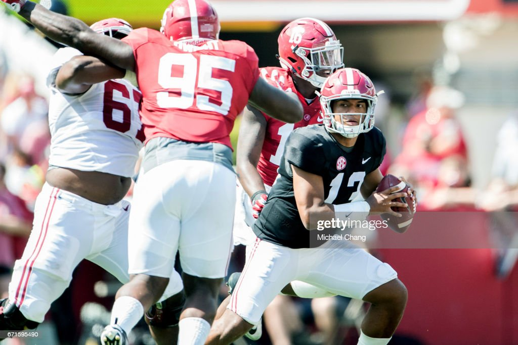 Quarterback Tua Tagovailoa #13 of the Alabama Crimson Tide looks to maneuver by defensive lineman Johnny Dwight #95 of the Alabama Crimson Tide during Alabama's A-Day spring practice game at Bryant-Denny Stadium on April 22, 2017 in Tuscaloosa, Alabama.