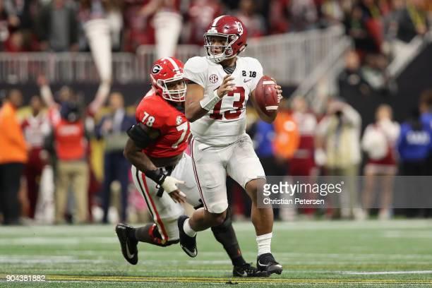 Quarterback Tua Tagovailoa of the Alabama Crimson Tide scrambles with the football ahead of defensive tackle Trenton Thompson of the Georgia Bulldogs...