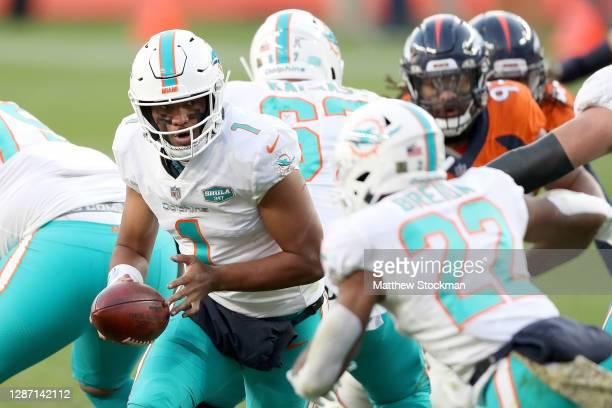Quarterback Tua Tagovailoa of the Miami Dolphins hands off the Matt Breida during the third quarter against the Denver Broncos at Empower Field At...