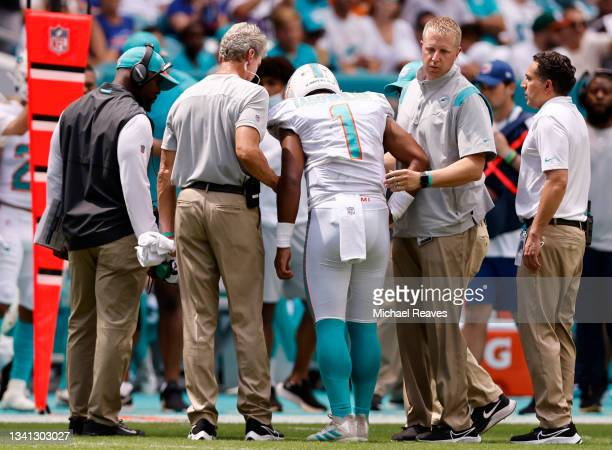 Quarterback Tua Tagovailoa of the Miami Dolphins is helped off the field in the first half of the game against the Buffalo Bills at Hard Rock Stadium...