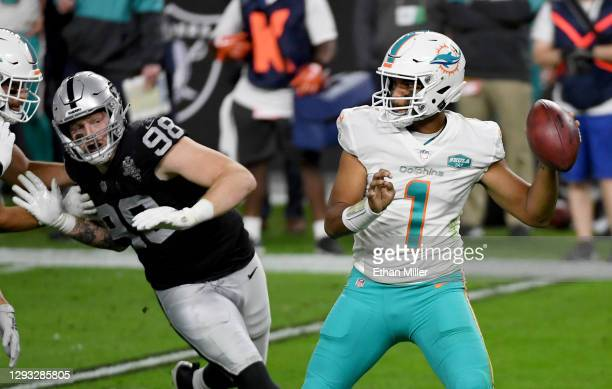 Quarterback Tua Tagovailoa of the Miami Dolphins throws under pressure from defensive end Maxx Crosby of the Las Vegas Raiders in the first half of...