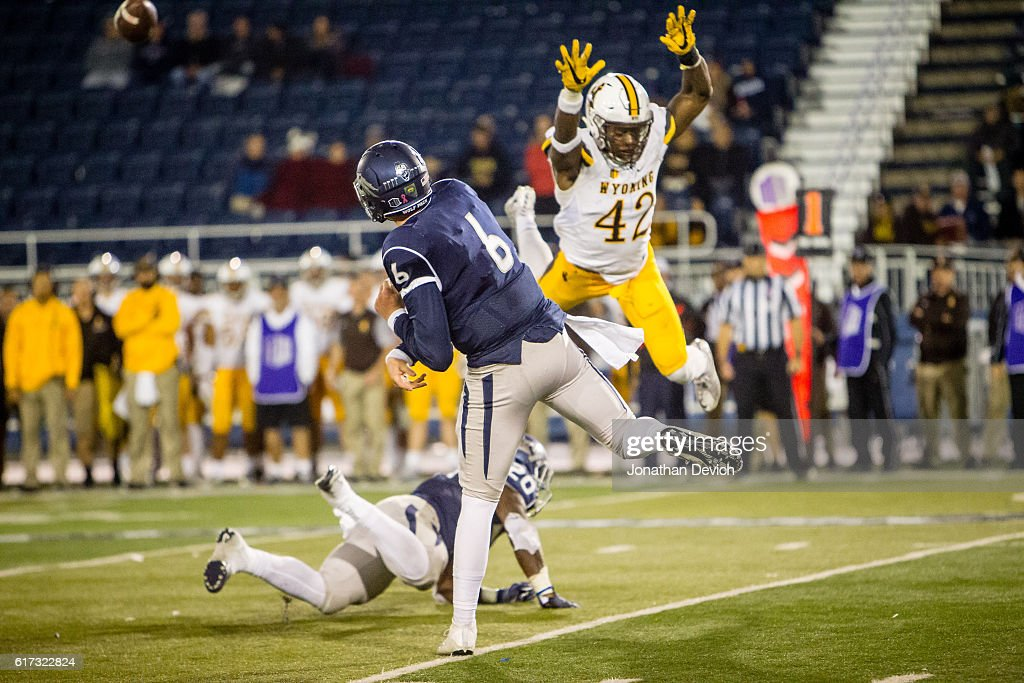 Quarterback Ty Gangi #6 of Nevada avoids safety Kevin Prosser #42 of Wyoming to throw a pass at Mackay Stadium on October 22, 2016 in Reno, Nevada.