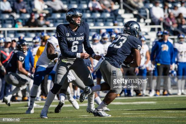 Quarterback Ty Gangi of the Nevada Wolf Pack hands the ball to running back Kelton Moore of the Nevada Wolf Pack during a play against the San Jose...