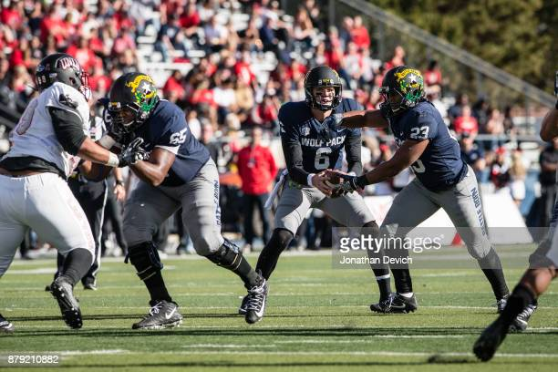 Quarterback Ty Gangi of the Nevada Wolf Pack passes the ball to running back Kelton Moore of the Nevada Wolf Pack to run against the UNLV Rebels at...