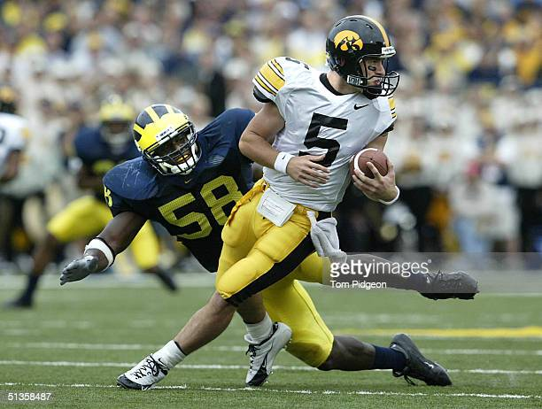 Quarterback Tyler Bergan of the University of Iowa is pressured by Roy Manning of the University of Michigan during the second quarter at Michigan...