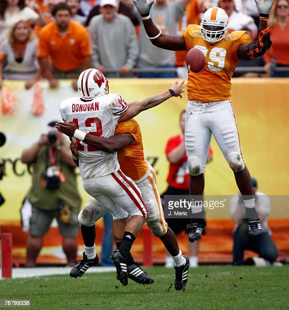 Quarterback Tyler Donovan of the Wisconsin Badgers just gets this pass off as defensive tackle J.T. Mapu of the Tennessee Volunteers tries to block...