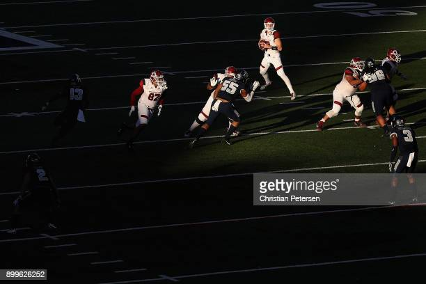 Quarterback Tyler Rogers of the New Mexico State Aggies drops back to pass during the first half of the Nova Home Loans Arizona Bowl game against the...