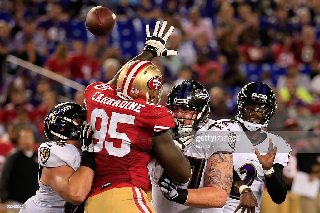 Quarterback Tyrod Taylor #2 of the Baltimore Ravens throws a pass while defensive end Cornellius Carradine #95 of the San Francisco 49ers tries to knock it down during the first half of an NFL pre-season game at M&T Bank Stadium on August 7, 2014 in Baltimore, Maryland.