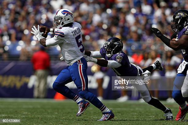 Quarterback Tyrod Taylor of the Buffalo Bills attempts to throw the ball as he is tackled by cornerback Lardarius Webb of the Baltimore Ravens in the...