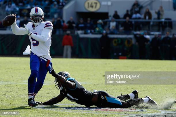 Quarterback Tyrod Taylor of the Buffalo Bills gets off a pass while being tackled by defensive end Yannick Ngakoue of the Jacksonville Jaguars in the...