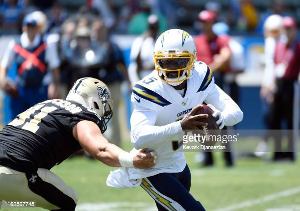 Quarterback Tyrod Taylor of the Los Angeles Chargers eludes a tackle by Trey Hendrickson of the New Orleans Saints during the first half of their...