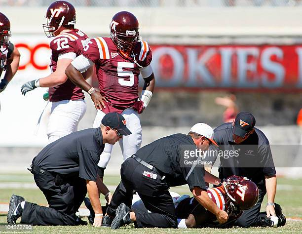 Quarterback Tyrod Taylor of the Virginia Tech Hokies watches as trainers help injured running back Ryan Williams against the East Carolina Pirates at...