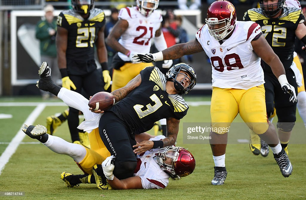 Quarterback Vernon Adams Jr. #3 of the Oregon Ducks injures his ankle as he is tackled by linebacker Anthony Sarao #56 as defensive tackle Cody Temple #98 of the USC Trojans during the third quarter of the game at Autzen Stadium on November 21, 2015 in Eugene, Oregon. The Ducks won the game 48-28.
