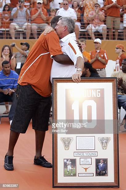 Quarterback Vince Young of the Tennessee Titans and formerly with the Texas Longhorns hugs coach Mack Brown as his number is retired before a game...