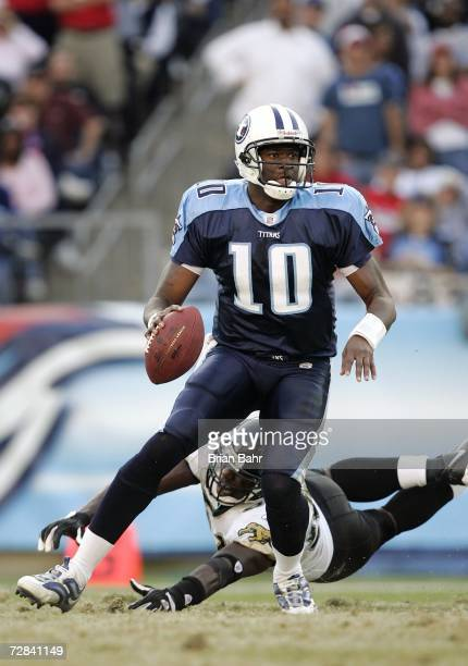 Quarterback Vince Young of the Tennessee Titans scrambles in the backfield under pressure from linebacker Clint Ingram of the Jacksonville Jaguars in...