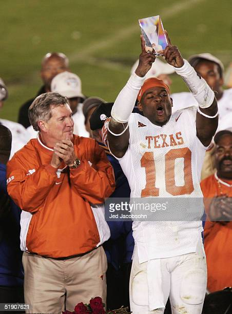 Quarterback Vince Young of the Texas Longhorns holds up his MVP trophy while head coach Mack Brown looks on after defeating the Michigan Wolverines...