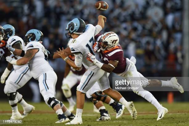 Quarterback Vito Priore of the Rhode Island Rams is hit as he attempts a pass by defensive back Chamarri Conner of the Virginia Tech Hokies in the...