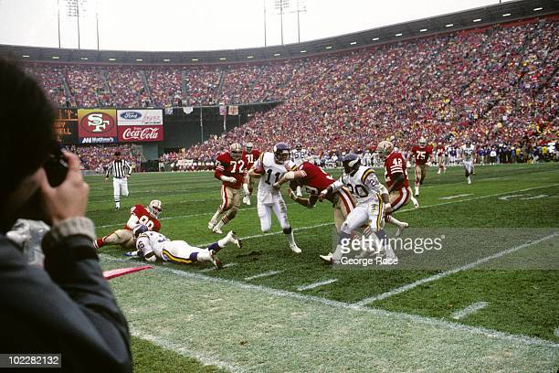 Quarterback Wade Wilson of the Minnesota Vikings gets pushed out of bounds during the 1987 NFC Divisional Playoffs against the San Francisco 49ers at...