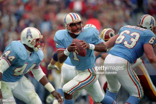 Quarterback Warren Moon of the Houston Oilers drops back to pass as running back Lorenzo Thomas and offensive lineman Mike Munchak block against the...