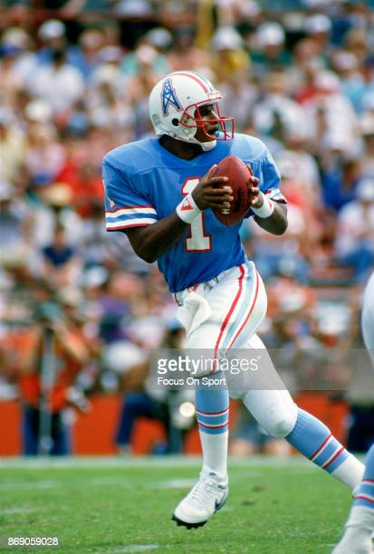 Quarterback Warren Moon of the Houston Oilers drops back to pass against the Miami Dolphins during an NFL football game circa 1986 at the Orange Bowl...