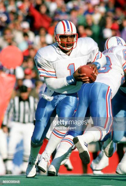 Quarterback Warren Moon of the Houston Oilers runs with the ball against the Buffalo Bills during the AFC Divisional Playoff game January 1 1989 at...