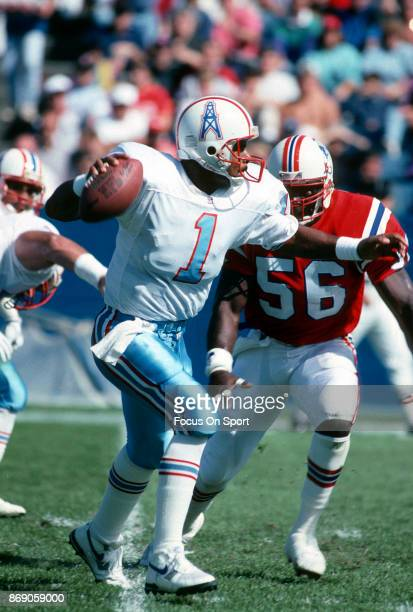 Quarterback Warren Moon of the Houston Oilers scrambles away from the pressure against the New England Patriots during an NFL football game September...
