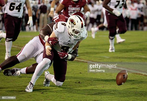 Quarterback Will Collins of the Louisiana Monroe Warhawks fumbles after being hit by defensive lineman Neville Gallimore of the Oklahoma Sooners...